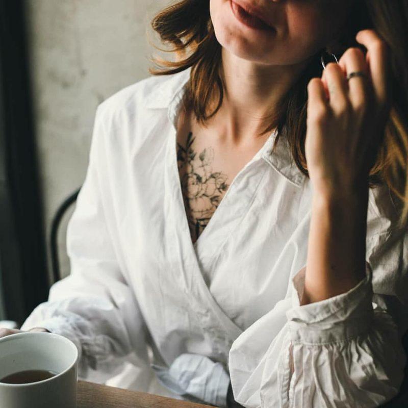 девушка с временной тату на груди в белой блузке