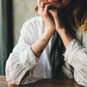 девушка с временной тату на руке в белой блузке