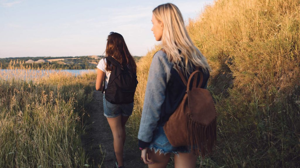 Best friends hiking together. Two young women travel with adventure. Girls walking in nature on summer vacation.
